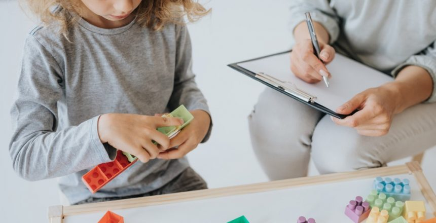 Young boy playing with blocks analyzed by school therapist